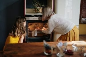 young girl and mother take a dish out of the oven