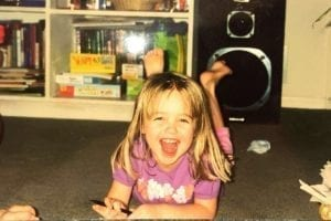 Community Engagement Coordinator Molly as a young girl lying on her stomach while smiling at the camera