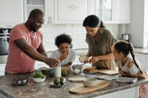 family of four made of dad, mom, son and daughter, making breakfast in a modern kitchen