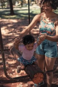 infant girl sitting on a seesaw while mom is holding her hands to support girl's dynamic sitting balance