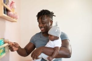 dad carrying his baby while pointing at book