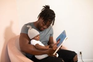 young father reading book to infant son