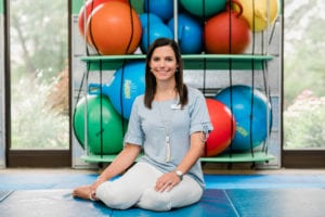 Speech Language Pathologist Danielle, seated in the Sensory Gym