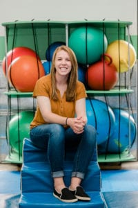 Occupational Therapist Maddy sitting in the Sensory Gym