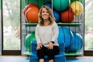 Occupational Therapist Miranda sitting in the sensory gym