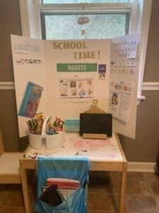 image of a children's table with a chair, ipad, and bucket of school supplie, a trifold display board with school information is set up on the table