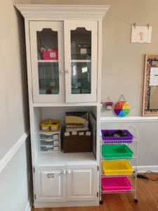 image of a white cabinet with upper and lower doors, upper doors are glass and show organized school supplies in colorful bins