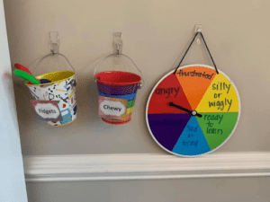 two buckets and a spinner board set up as a sensory station containing chewies, fidgets and a choice board to identify emotion