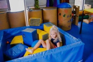 Child sitting in a large blue ball pit filled with blue and yellow foam blocks