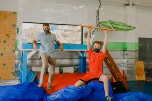 Child swings on a trapeze bar with a therapist standing behind him, leaning against a lofted platform