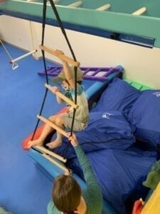 Above shot of a boy in a hat climbing a wobbly rope ladder while a therapist stands below