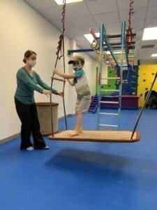 Therapist pulls rope platform swing handles while boy in hat stands on the platform waiting to be released
