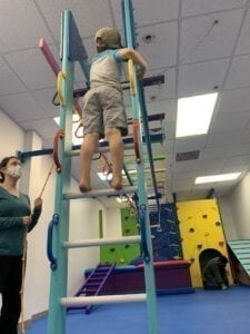 Boy climbing a ladder to monkey bars with therapist standing near by
