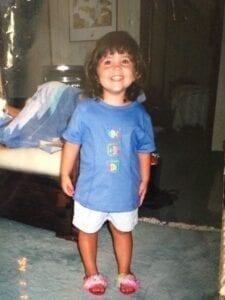 Speech-language pathologist Natalie as a young girl wearing a blue shirt