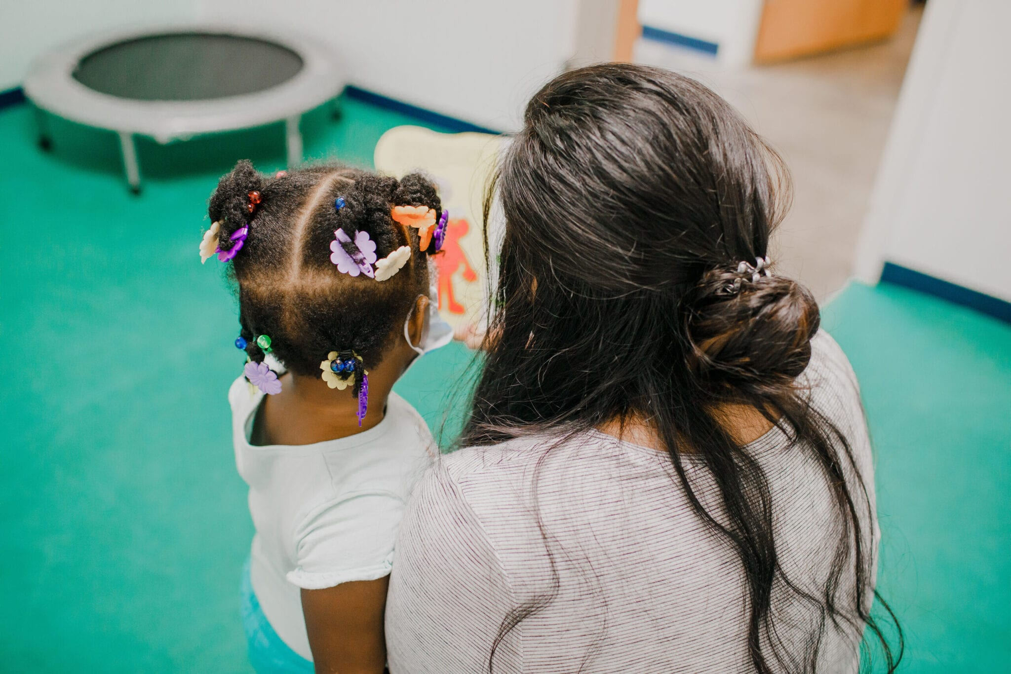 Speech-language pathologists reading with a young girl