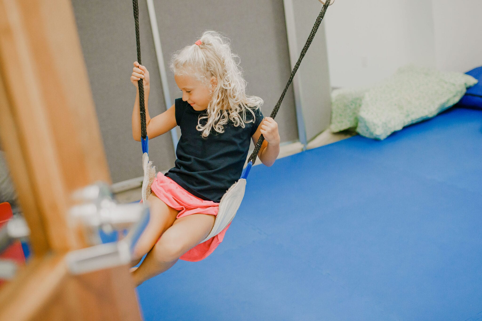 Girl swinging on a frog swing in the small sensory gym