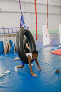 Young boy in a tire swing, reaching for toys on the floor during Occupational Therapy in a Sensory Gym