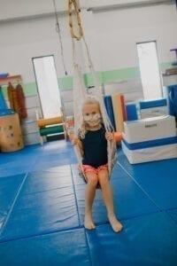 Girl swinging on a hammock swing in the Sensory Gym