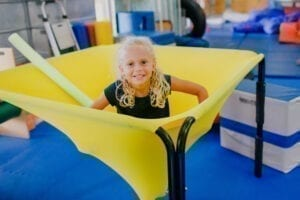Young girl sitting in the middle of a cloud swing in the Sensory Gym