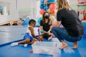 Two Female therapist working with a child in a Sensory Gym