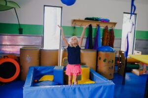 Young girl playing catch with a blue therapy ball while standing in a foam pit