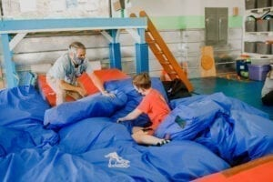 Boy crashing into the floor pillows while an Occupational Therapist watches