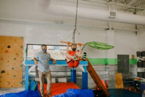Boy swinging from a trapeze swing in the Sensory Gym