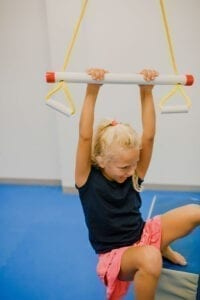 Girl hanging from the trapeze swing