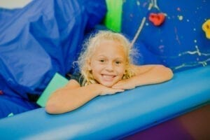Young girl smiling from the foam pit in the Sensory Gym