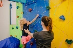 Girl climbing up a rock climbing wall with an Occupational Therapist helping