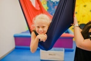 Young girl in a cloud swing with an occupational therapist
