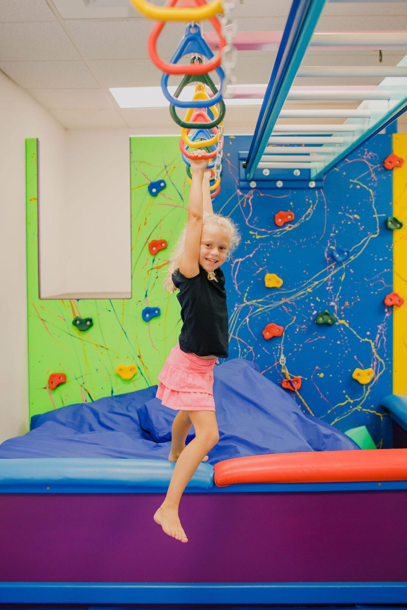 Young girl swinging on the monkey bars in the Sensory Gym