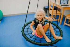 Girl swinging on a Spider Web Tree Swing