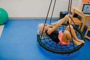 Girl enjoying swinging on a Spider Web Tree Swing