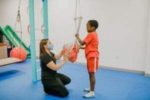 Boy and Occupational Therapist putting Elmo into a net swing