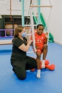 Boy sitting in a net swing while an occupational therapist pushes the swing