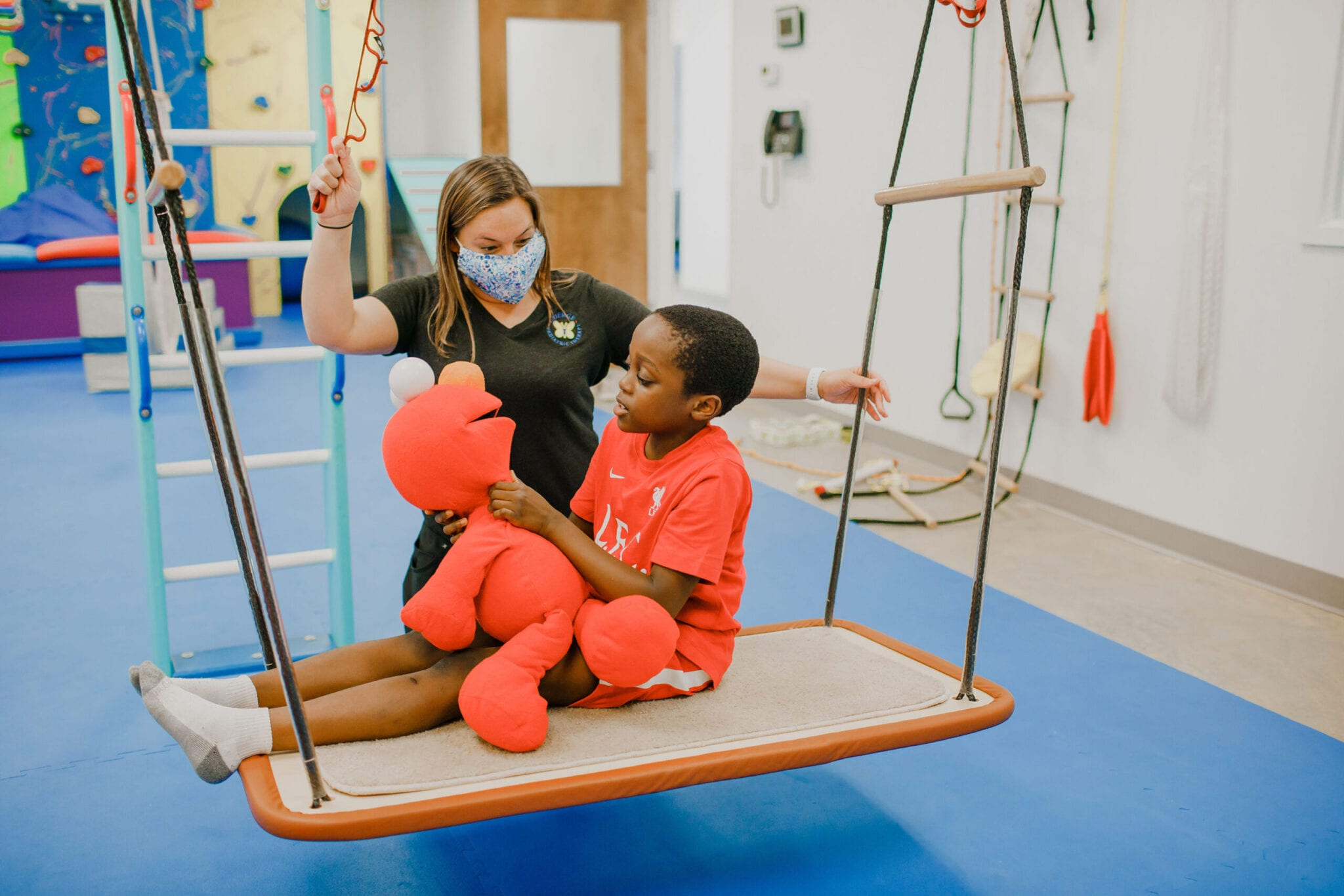 Boy sitting on the platform swing with an Elmo doll while an Occupational Therapist rocks the swing