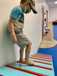 young boy walking down a blue and red plank in a sensory gym
