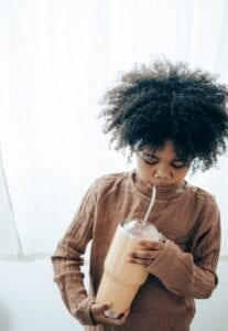 young child drinking from a straw