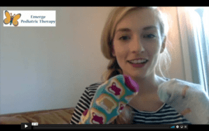 Blonde, female, therapist sitting against a white wall. she has colorful socks on her hands as sock puppets, holding home up at the bottom of the screen.