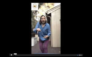 white, female therapist in a denim shirt and maroon pants looks excited as she dances towards the camera. butterfly logo in upper left corner.