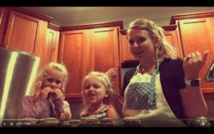 Two small blonde girls stand next to their blonde mother in a kitchen with brown cabinets