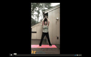 White, female therapist doing a jumping jack, dressed in a green top and black yoga pants, jumping on a pink yoga mat