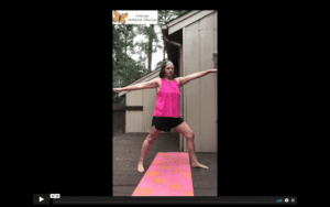 White, female, therapist in black gym short and bright pink top does warrior 2 yoga pose on a pink yoga mat