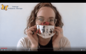 female therapist with blonde curly hairs, sits in front of a white wall, holding a colorful mask in front of her face. butterfly logo in the upper left corner of the screen
