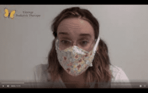 Female therapist with blonde curly hair and glasses sits in front of a white wall while wearing a floral face mask