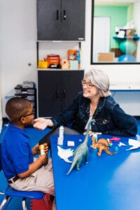 white, female therapist with gray hair touches the face of a young black boy as they play with dinosaurs and work on articulation