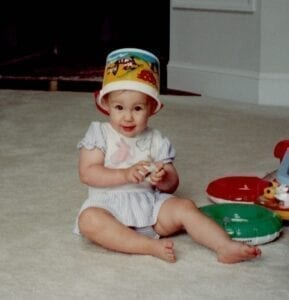 white, female, toddler in a pale summer romper sits on the floor with a colorful bucket on her head