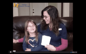 White, brunette, female therapist in glasses sits on a leather sofa with her daughter