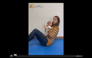 White, female therapist wearing a yellow and white striped shirt, sits in a crunch position while holding a baby doll to her chest. She looks at the camera.